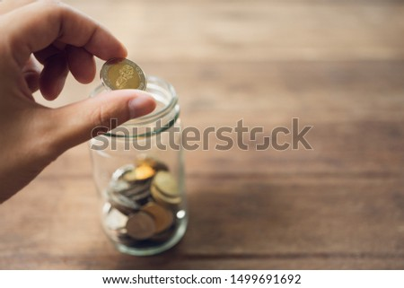 Business men Put the coin in a glass jar To save money, save money on investments, spend money when needed And use in the future. Investment concept. Savings with copy spaces. #1499691692
