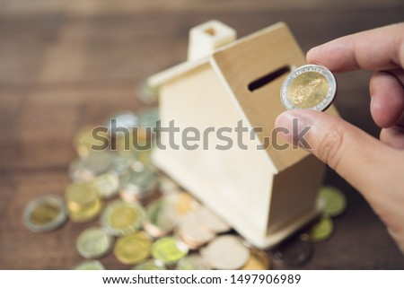 Business men Put the coin in House style piggy bank To save money, save money on investments, spend money when needed And use in the future. Investment concept. Savings with copy spaces. #1497906989