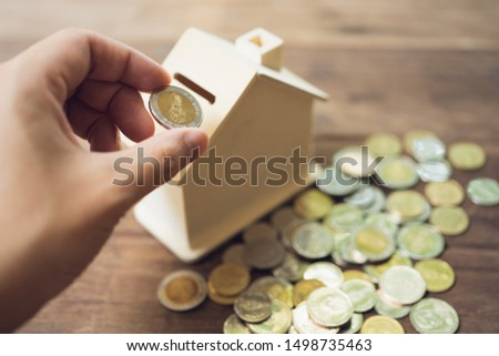 Business men Put the coin in House style piggy bank To save money, save money on investments, spend money when needed And use in the future. Investment concept. Savings with copy spaces. #1498735463