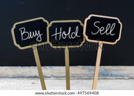 Business message Buy, Hold or Sell written with chalk on wooden mini blackboard labels, defocused chalkboard and wood table in background #497569408