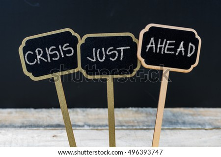 Business message CRISIS JUST AHEAD written with chalk on wooden mini blackboard labels, defocused chalkboard and wood table in background #496393747
