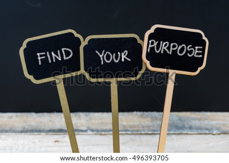 Business message FIND YOUR PURPOSE written with chalk on wooden mini blackboard labels, defocused chalkboard and wood table in background #496393705