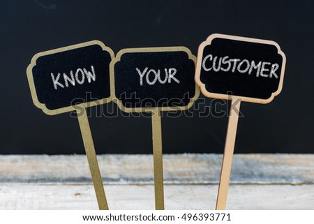 Business message KNOW YOUR CUSTOMER written with chalk on wooden mini blackboard labels, defocused chalkboard and wood table in background #496393771