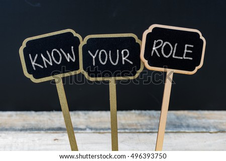 Business message KNOW YOUR ROLE written with chalk on wooden mini blackboard labels, defocused chalkboard and wood table in background #496393750