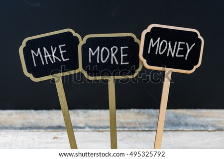 Business message MAKE MORE MONEY written with chalk on wooden mini blackboard labels, defocused chalkboard and wood table in background #495325792
