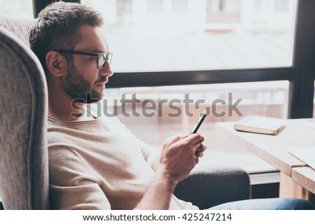 Business message. Side view of handsome man using his smartphone while sitting in chair in front of window
