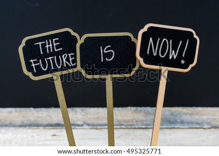 Business message THE FUTURE IS NOW written with chalk on wooden mini blackboard labels, defocused chalkboard and wood table in background #495325771