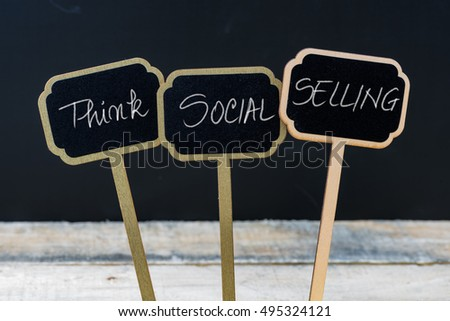 Business message THINK SOCIAL SELLING written with chalk on wooden mini blackboard labels, defocused chalkboard and wood table in background #495324121