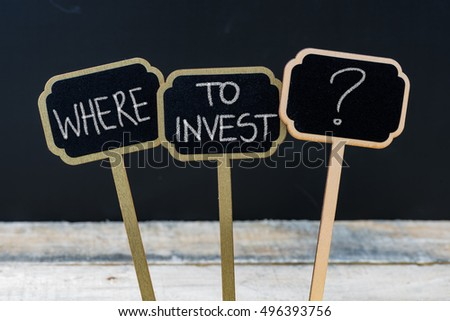 Business message WHERE TO INVEST ? written with chalk on wooden mini blackboard labels, defocused chalkboard and wood table in background #496393756