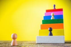 Business metaphor of businessman climbing colorful career stairs on yellow background. Going up concept using stairway of wood blocks. Achieving success. Business competition. Career, social status.