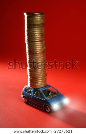 Business metaphor, toy car with huge column of golden coins over red [Photo Illustration]