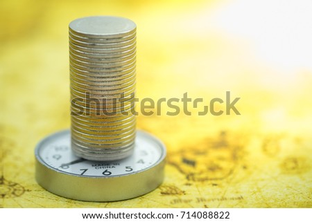 Business, money and time concept. Close up of stack of silver coins on watch and on world map.