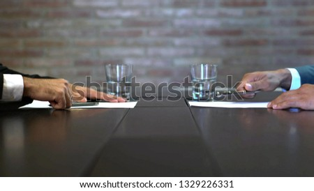 Business negotiations close up, two businessmen discussing analyzing financial data, male hand holding pen, convincing client to sign contract, emphasizing important information, negotiating skills -  #1329226331