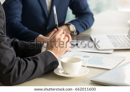 Business negotiations close up, two businessmen discussing analyzing financial data, male hand holding pen, convincing client to sign contract, emphasizing important information, negotiating skills