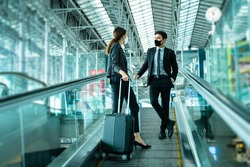Business New normal concept.Traveler businessman and woman wear face mask on escalator at terminal airport,New normal of people to awareness and protection for prevent coronavirus or covid-19 pandemic