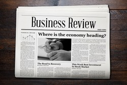 Business Newspaper on wooden background.