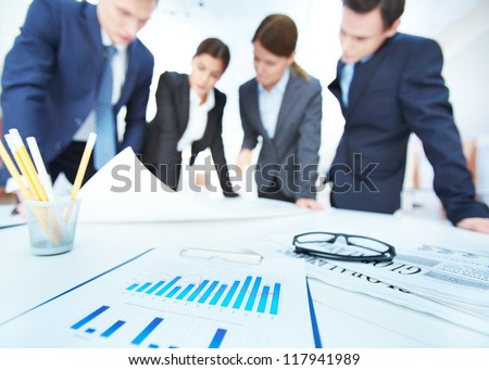 Business objects on background of engineers discussing blueprint at meeting