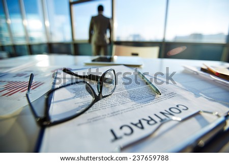 Business objects on workplace with businessman standing on background