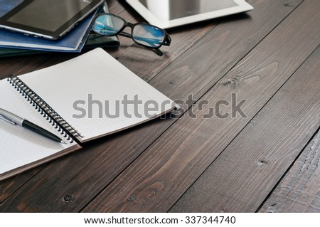 Business Objects (tablet computer, glasses for computer, notebook, leather folders, pen). Open notebook with blank pages on wooden office desk close up. Top view. Free space for text. Copy space