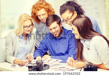 business, office and startup concept - smiling creative team with photocameras and images working in office
