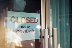 Business office or store shop is closed, bankrupt business due to the effect of novel Coronavirus (COVID-19) pandemic. Unidentified person wearing mask hanging closed sign in background on front door.
