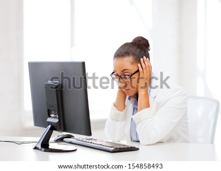 business, office, school and education concept - stressed african businesswoman with computer at work