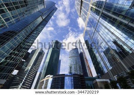 Business office skyscrapers, looking up at high-rise buildings in commercial district, architecture raising to the blue sky with white clouds, bottom view