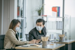 Business office working together at new normal social distance with table shield partition reduce infection of coronavirus covid-19 pandemic. Social and business distancing new normal lifestyle.