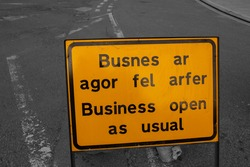 Business open as usual sign, in English and Welsh, warning of roadworks ahead.  With selective colour