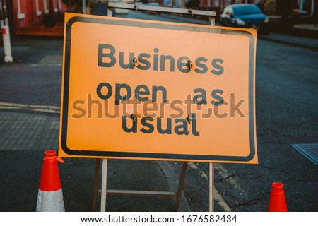 Business open as usual. Yellow sign stating business open as usual during lockdown and road works. Business open as usual sign on road. Business open as usual sign during coronavirus covid-19 pandemic Foto d'archivio ©