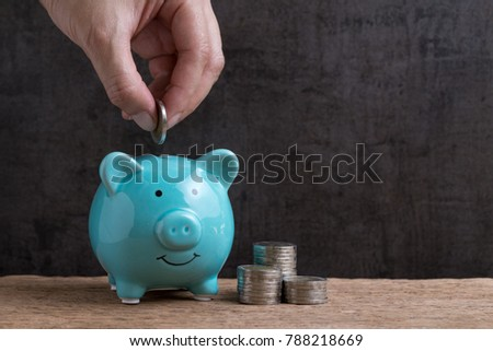 Business or finance saving concept with hand putting coin into blue piggy bank with stack of coins beside on wooden table and dark black background with copy space. #788218669