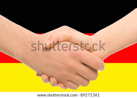 Business or friendly handshake between man and woman on background of German flag