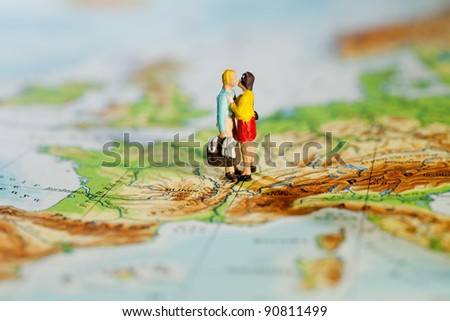 Business Or Personal Travel Concept. Two miniature figurines of a man carrying luggage and his wife embracing while standing on a map of Europe.