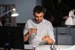 business, overwork and deadline concept - businessman taking medicine pills at night office