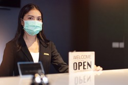 Business owner attractive young Asian woman in suitcase we're open sign on front counter welcoming clients to new hotel.Happy waiter with protective face mask holding open sign while stand at hotel .