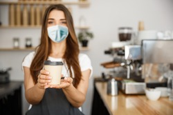 Business Owner Concept - Beautiful Caucasian Barista in face mask offers disposable take away hot coffee at the modern coffee shop