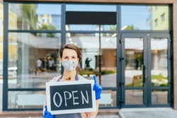 Business owner Hispanic woman wear protective face mask holding open sign at her at her zero waste grocery shop outdoor. Business open again after coronavirus covid-19. Supporting local business.