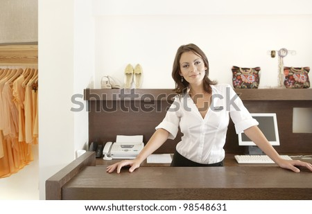 Business owner leaning on her fashion store's desk, feeling proud.