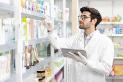 Business owner Middle eastern male pharmacist checking stock drugstore using digital tablet technology in modern pharmacy.