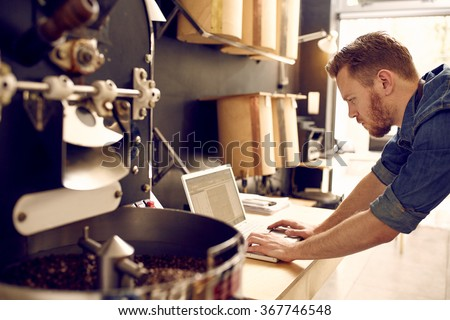 Business owner of a coffee roastery checking his laptop