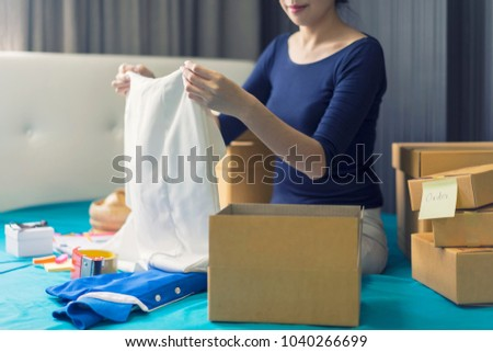Business owner taking and packing online order to delivery. Freelance woman seller prepare parcel box of product for deliver to customer. Online selling, e-commerce, shipping concept.