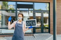 Business owner woman wear protective face mask holding open sign at her zero waste grocery shop outdoor, open again after lock down due to outbreak of coronavirus covid-19. Supporting local business.