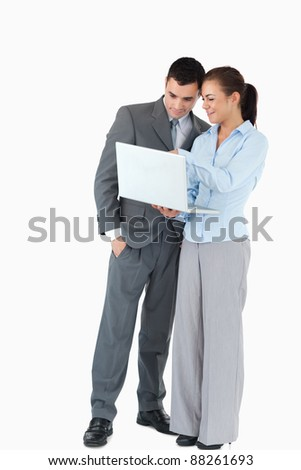 Business partner looking at a laptop together against a white background