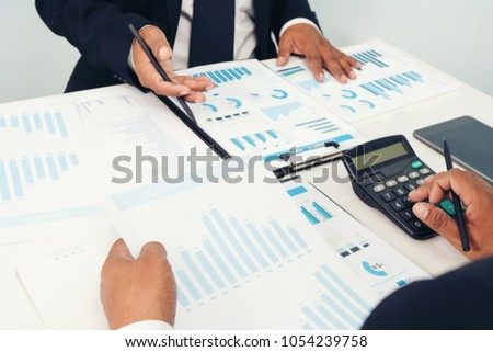 business partner marketing discussing market research and brainstorming with colleagues in a meeting.Team meeting in conference room looking at documents Financial Planning Report in excel spreadsheet