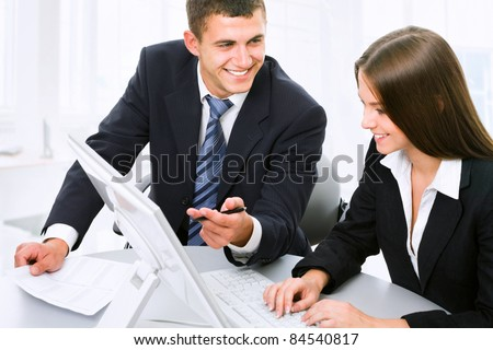 Business partners are discussing a new project while sitting at the computer