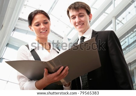 Business partners are working together in the lobby of a modern office center