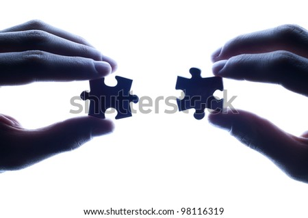 business partners combining puzzle pieces against bright light