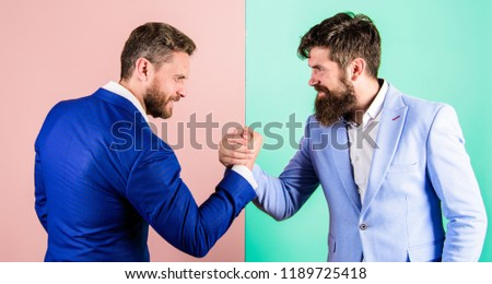 Business partners competitors office colleagues tense faces ready to compete in arm wrestling. Business competition and confrontation. Hostile or argumentative situation between opposing colleagues.