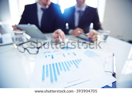 Business partners discussing financial documents at office