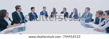 business partners gathered round a table and discuss the finances #744416533